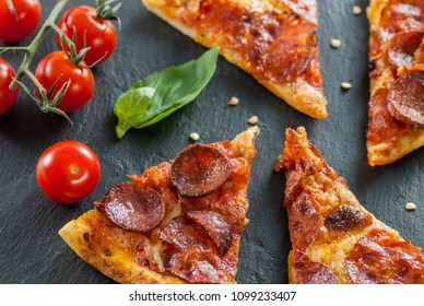 delicious fresh cooked slices of pepperoni pizza on slate with cherry tomatoes red pepper and basil leafs