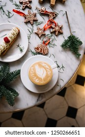 Delicious fresh cup of cappuccino coffee, spruce branches, eclair and Christmas festive decorations on the marble table background in a cafe, top view, flat lay