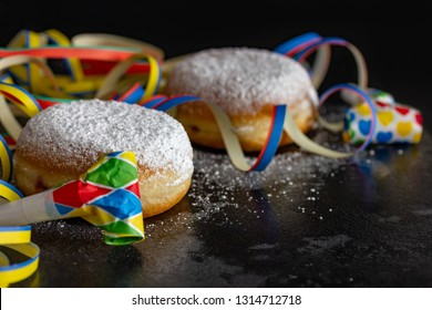 delicious fresh donuts, streamers and prats in front of black background