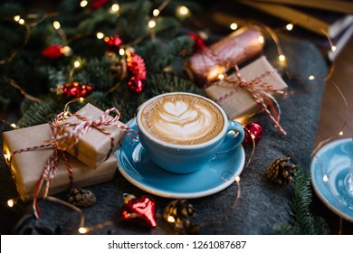 Delicious fresh festive morning cappuccino coffee in a ceramic blue cup on the warm cover with little wrapped gifts, red ornamentals, fireflies and spruce branches