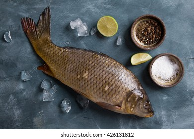 Delicious fresh fish (carp) on dark vintage background for healthy food, diet or cooking concept, selective focus