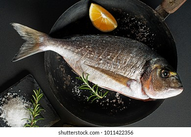 Delicious fresh fish on dark vintage background. Healthy food diet or cooking concept