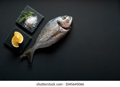 Delicious fresh gilt-head fish on dark vintage background. Healthy food diet or cooking concept
