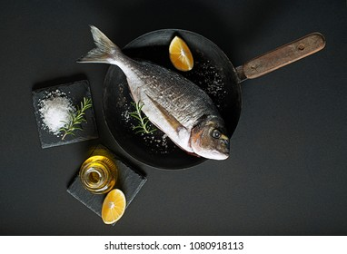 Delicious fresh gilt-head fish on dark background. Healthy food diet or cooking concept