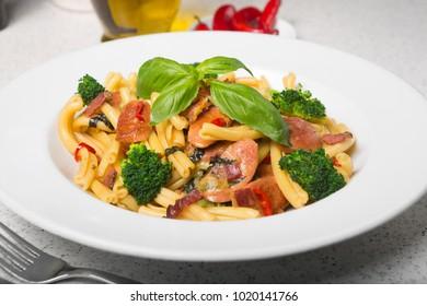 A delicious fresh gourmet Italian strozzapreti pasta dish, with pancetta, italian sausage, broccoli, vegetables, topped with fresh basil.