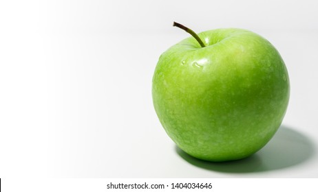 Delicious fresh Granny Smith apple on a white background with space to left