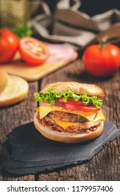 delicious fresh home made burger with lettuce, cheese, onion and tomato on black stone and wood background