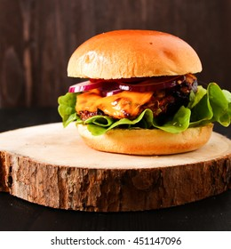 Delicious fresh homemade burger on dark serving board with spicy tomato sauce herbs over dark wooden background. Top view, copy space.