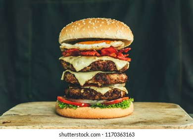 Delicious Fresh Homemade Burger With Fresh Vegetables on Chopping Wood And Black Wallpaper Background