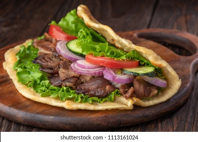 Delicious fresh homemade sandwich with roasted meat, tomato, onions and lettuce on wooden board on dark wooden table. Doner kebab. Healthy food concept.