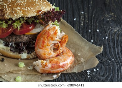Delicious fresh homemade surf and turf  burger on wooden table