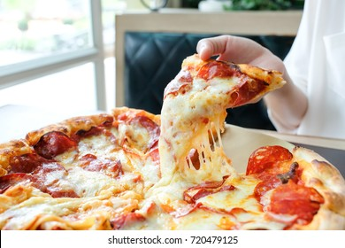 Delicious  fresh hot Italian pizza slice with melting cheese on wooden table.