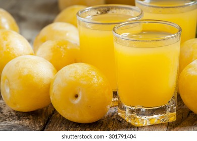 Delicious fresh juice of yellow sweet plums in a glass on the old wooden background, selective focus