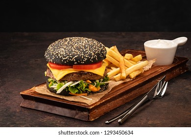 Delicious fresh juicy homemade cheeseburger in a black bun with tomatoes and salad. Beef Burger with Cheese and Vegetables