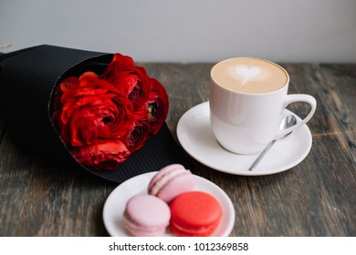 Delicious fresh morning cappuccino coffee with french macarons cookies of red an pink color and red ranunculus flower bouquet on the rustic wooden table background, festive  romantic setup