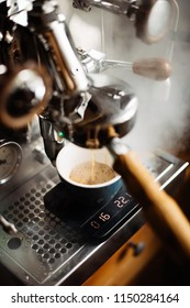 Delicious fresh morning espresso coffee with beautiful crema puring through the bottomless portafilter with wooden handle into ceramic cup, steam on the background