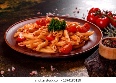 Delicious fresh paste with tomato sauce with spices and herbs on a dark background. Mediterranean cuisine