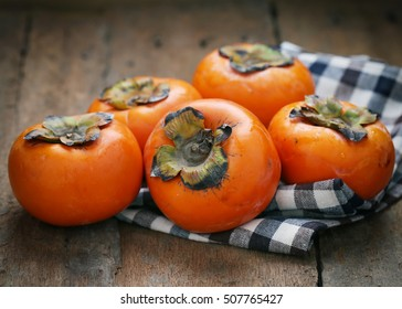 Delicious fresh persimmon fruit on wooden table.