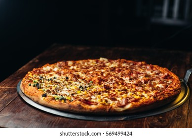 Delicious fresh pizza served on wooden table, brown background with copy space