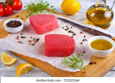 delicious Fresh raw tuna fish steaks prepared for cooking on cutting board with thyme leaves, lemon slices. olive oil and cherry tomatoes on background, view from above, close-up