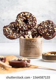 Delicious fresh Red Apple slices in melted chocolate with chopped almond nuts on wooden popsickle sticks, White background, healthy dessert.