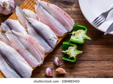 Delicious and fresh, spiced and seasoned raw Fish fillets on a cutting board, on top of a wooden background, with bell peppers, whole and garlic cloves as garnish