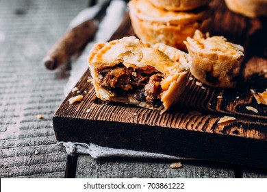 Delicious Fresh Traditional Australian meat mini pie on the wooden board on table background, closeup with copy space, rustic style