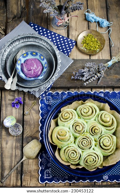 Delicious freshly baked cinnamon rolls with matcha tea and blackcurrant cream