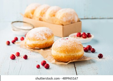 Delicious freshly baked doughnuts with powdered sugar and fruit jam on blue wooden background. Breakfast concept, Selective focus.
