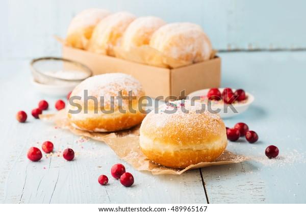 Délicieux beignets fraîchement cuits avec du sucre en poudre et de la confiture de fruits sur fond bleu bois. Concept petit-déjeuner, mise au point Sélective.
