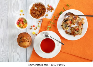 delicious freshly baked Homemade Banana Nut raisin Muffin on table and one muffin was broken into pieces on plate and served with cup of tea, view from above