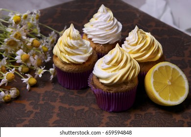 delicious freshly baked homemade lemon muffins cupcakes with butter cream with  bouquet of chamomile flowers , copy space