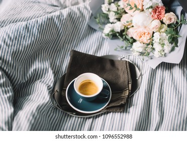Delicious freshly brewed espresso coffee in bed in a ceramic blue cup with a saucer and a flower bouquet of mattiolas, peony, roses, carnations on the background