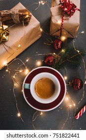 Delicious freshly brewed morning espresso coffee with beautiful crema on the dark grey background with spruce branches, holiday presents, candy cane, red Christmas decoration balls and fireflies, top