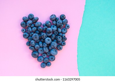 Delicious freshly picked bluberry in a form of heart on blue and pink background with copyspace. Healthy food concept.