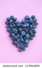Delicious freshly picked bluberry in a form of heart on pink background. Healthy food concept.