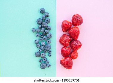 Delicious freshly picked bluberry and strawberry on blue and pink background. Blueberry border design.