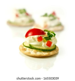 Delicious freshly prepared cream cheese canapes with cucumber, chilli peppers and tomatoes with a parsley garnish against a white background. Copy space.