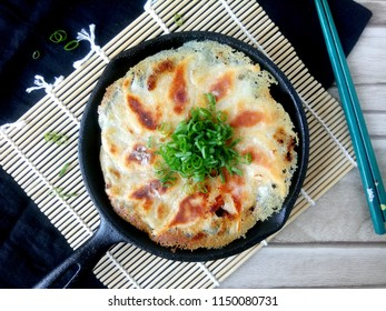 Delicious fried dumplings with green onion on cast iron skillet.