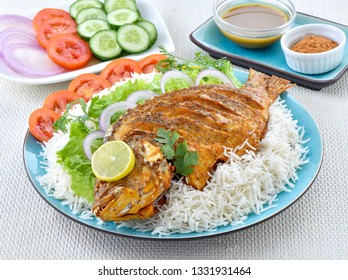 Delicious fried fish with boiled rice and salad