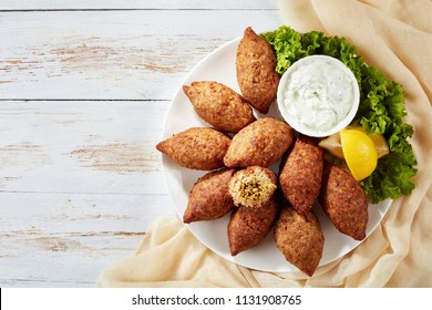 delicious fried kibbeh with yogurt sauce in a bowl served on a plate with lettuce and lemon slices on old wooden table, classic lebanese recipe, horizontal view from above