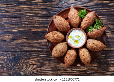 delicious fried kibbeh with yogurt sauce in a bowl served on a clay plate on an old dark wooden table, classic recipe, view from above, copy space, flat la