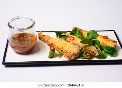 Delicious fried mozzarella sticks with tomato sauce served with greens