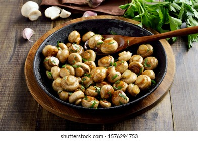 Delicious fried mushrooms in frying pan on wooden table