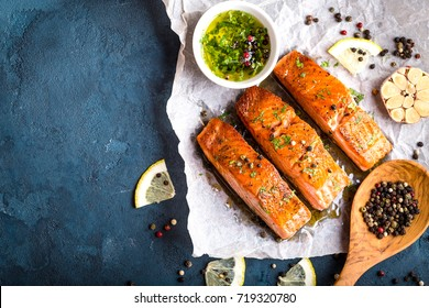 Delicious fried salmon fillet, seasonings on blue rustic concrete background. Cooked salmon steak with pepper, herbs, lemon, garlic, olive oil, spoon. Space for text. Fish for dinner. Healthy eating