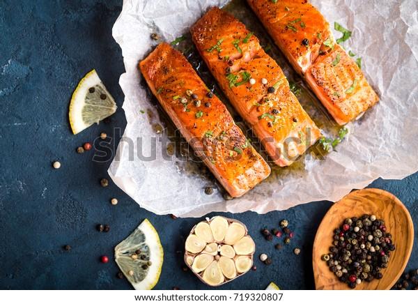 Chutné smažené filé z lososa, koření na modrém rustikálním betonovém pozadí. Vařený steak z lososa s pepřem, bylinkami, citronem, česnekem, olivovým olejem, lžící. Grilované ryby. Ryby na zdravou večeři. Detailní