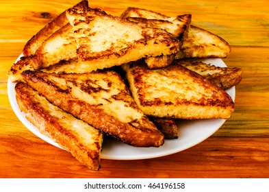 Delicious fried toast on a white plate. On a wooden background.