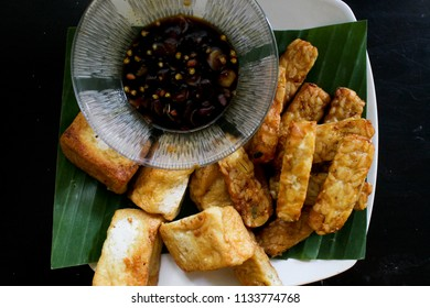 Delicious fried tofu and tempe with hot soy sauce on the white plate and green banana leaf