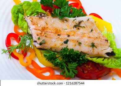 Delicious fried trout fillets served with baked potato, bell peppers, tomatoes and greens