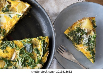 Delicious frittata with kale and potatoes in pan and slice on plate.